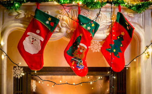 colorful christmas stockings hanging over fireplace with healthy treats inside